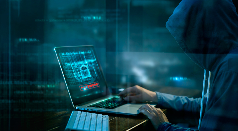 dark figure coding on laptop computer