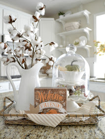 kitchen countertop fall decor with a small tray, fall sign, pumpkins and white vase