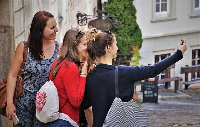 4 women making a selfie while traveling for cheap