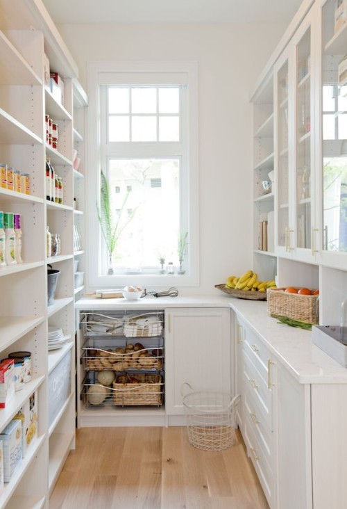 modern white pantry with natural light, floor to ceiling shelving, glass door cabinets, white countertops, wire shelving and wood floors