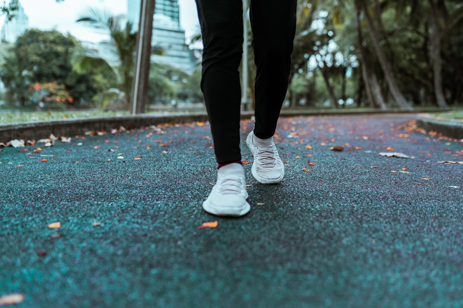 white sneakers jogging on an asphalt walkway in a park