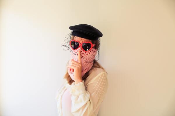 """Mulher com boina preta, um óculos de coração vermelho e um pano rosa amarrado no nariz e boca, fazendo um sinal de """"shiu"""" com o dedo."""