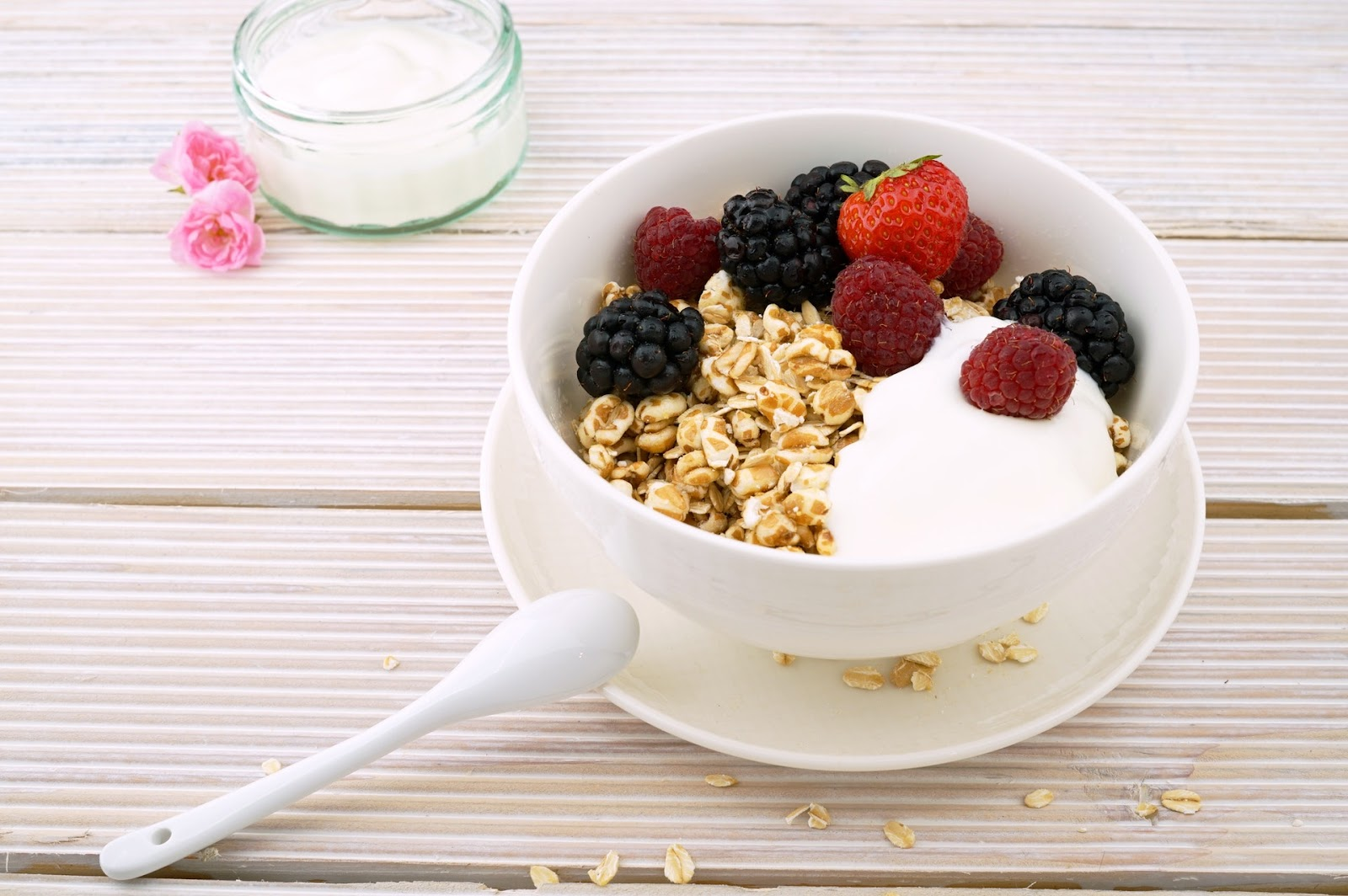 Yoghurt and fresh berries in a bowl with a spoon.