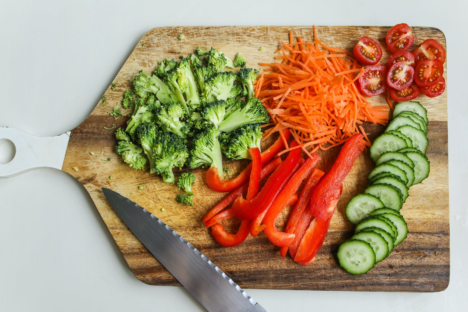 chopping board full of healthy food such as broccoli, carrots strips, cucumber, peppers and tomatoes