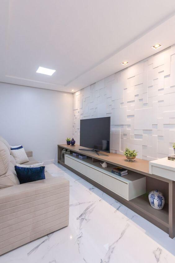 Sala com piso porcelanato reproduzindo mármore branco, revestimento 3D branco na parede de fundo, rack comprida amadeirada com TV e sofá branco com almofadas azuis.
