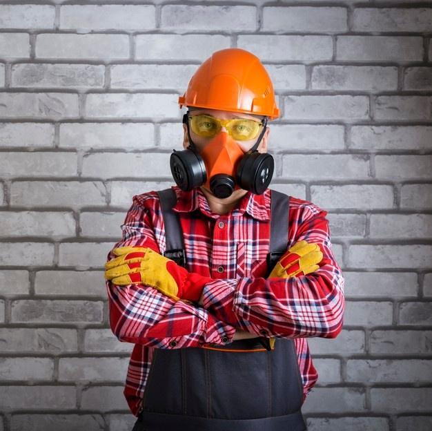 Retrato de trabalhador usando equipamento de proteção. construtor com equipamento de segurança contra superfície de parede de tijolo. Foto Premium
