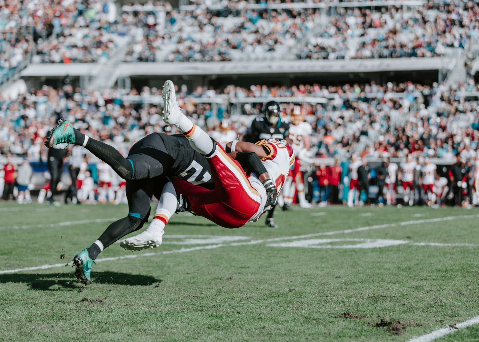 The definitive guide to live sports streaming - one football player tackles another.