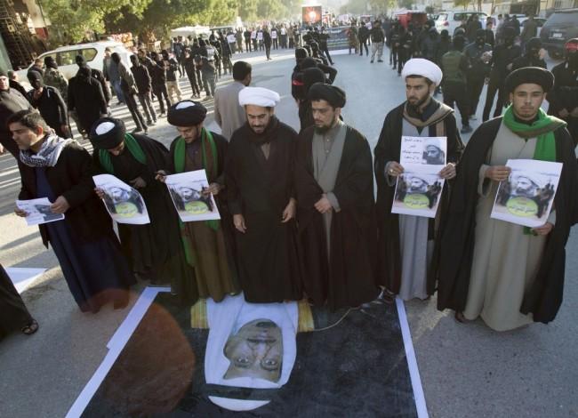 Шиитские священники топчут портрет саудовского короля в знак протеста против казни шейха Нимра ан-Нимра. Фото REUTERS/Scanpix