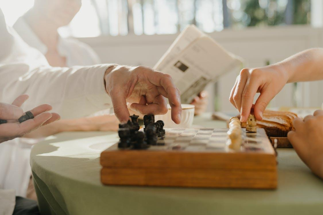 Person Playing Chess Game on Table