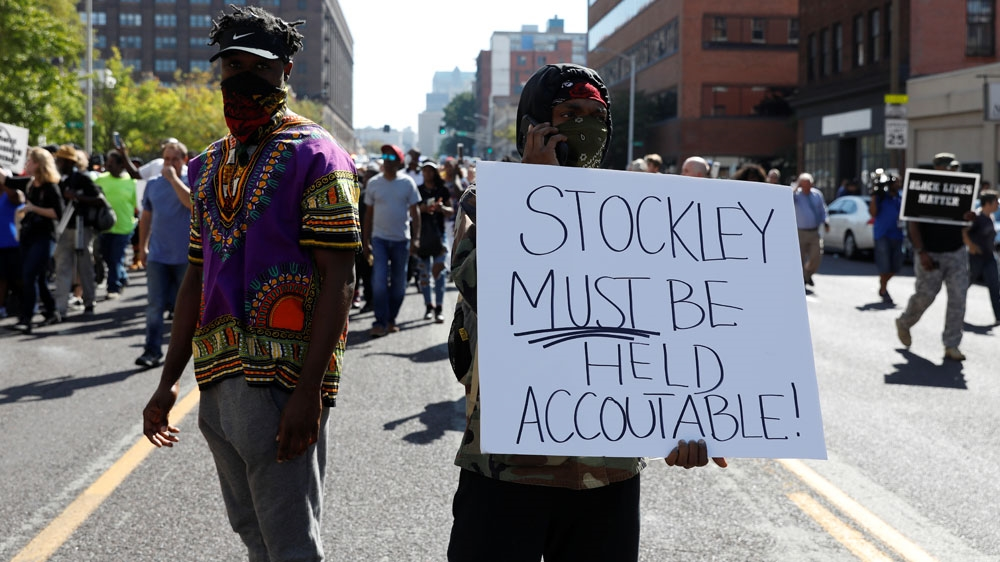 men holding a sign reading Stockley must be held accountable with other protesters in the background