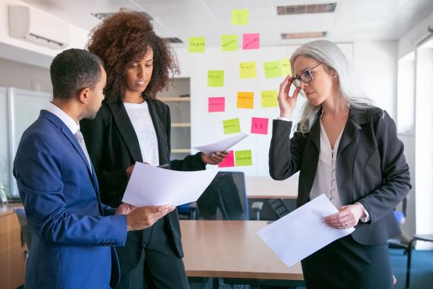 A imagem apresenta uma reunião de profissionais criando estratégias de marketing e analisando informações