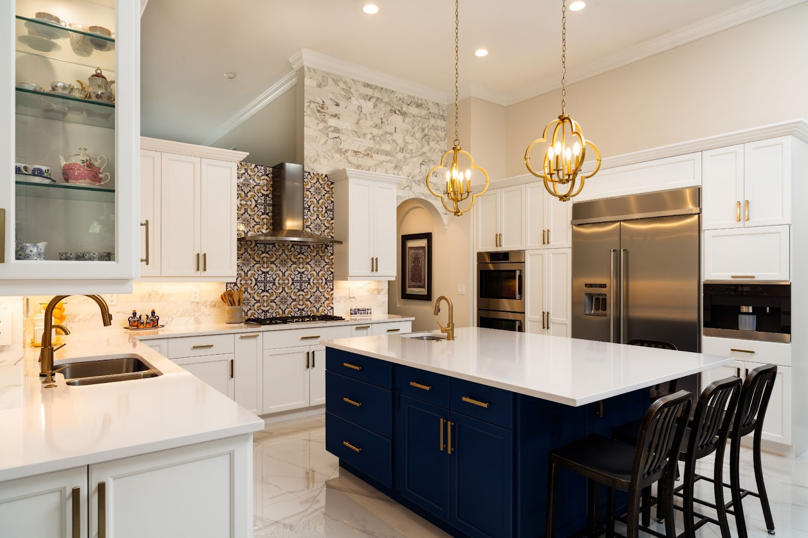 a luxurious kitchen with white and black cabinets, an island, and a beautiful backsplash