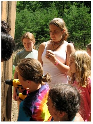 Overseeing use of tools older campers guide young ones while constructing an out building.