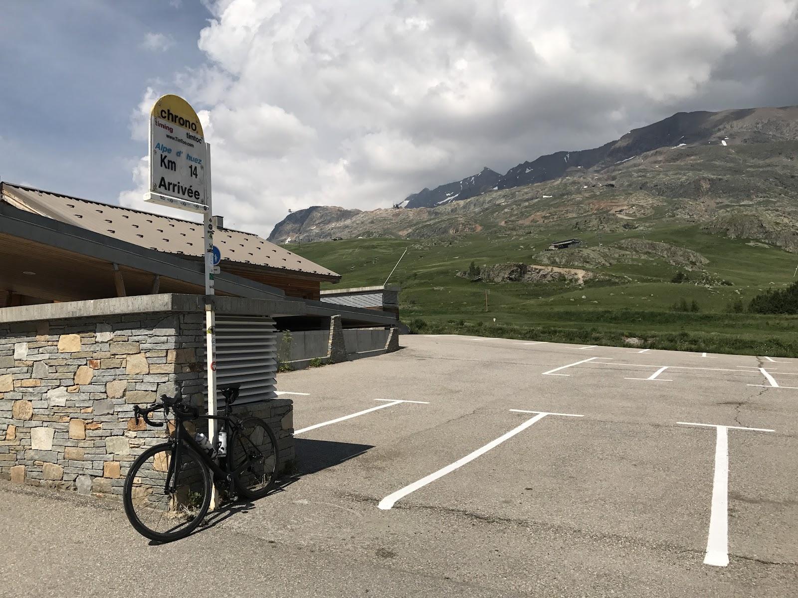 Riding bike up Alpe d'Huez - finish line and bike next to Alpe d'Huez Tour de France sign.