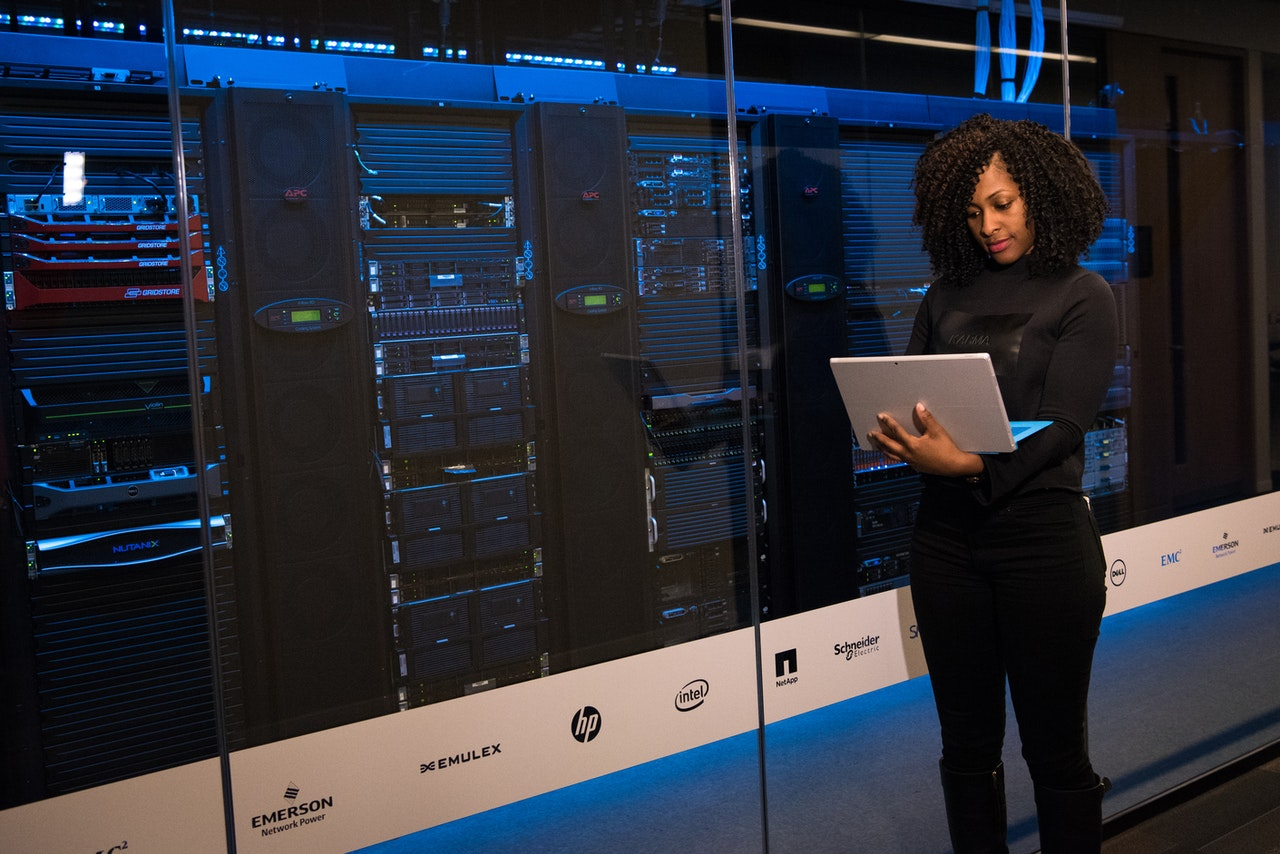 Woman standing in front of a server holding a laptop.