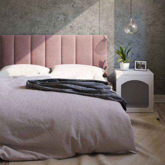 Quarto com cama de casal com cabeceira rose, parede com cimento queimado, luminária pendente e criado mudo branco.