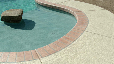 The corner of a rounded swimming pool with red tile around the pool and a beige colored concrete with texture around the pool.
