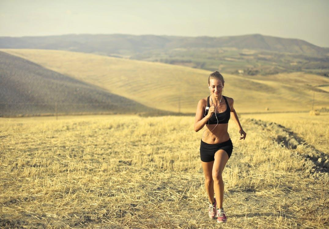 Cheerful sportswoman running along hill in summer