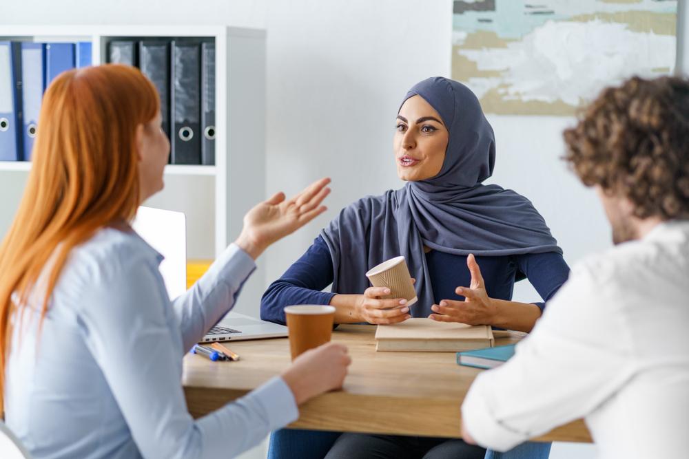 Uma mulher muçulmana conversando com outra mulher no ambiente de trabalho.