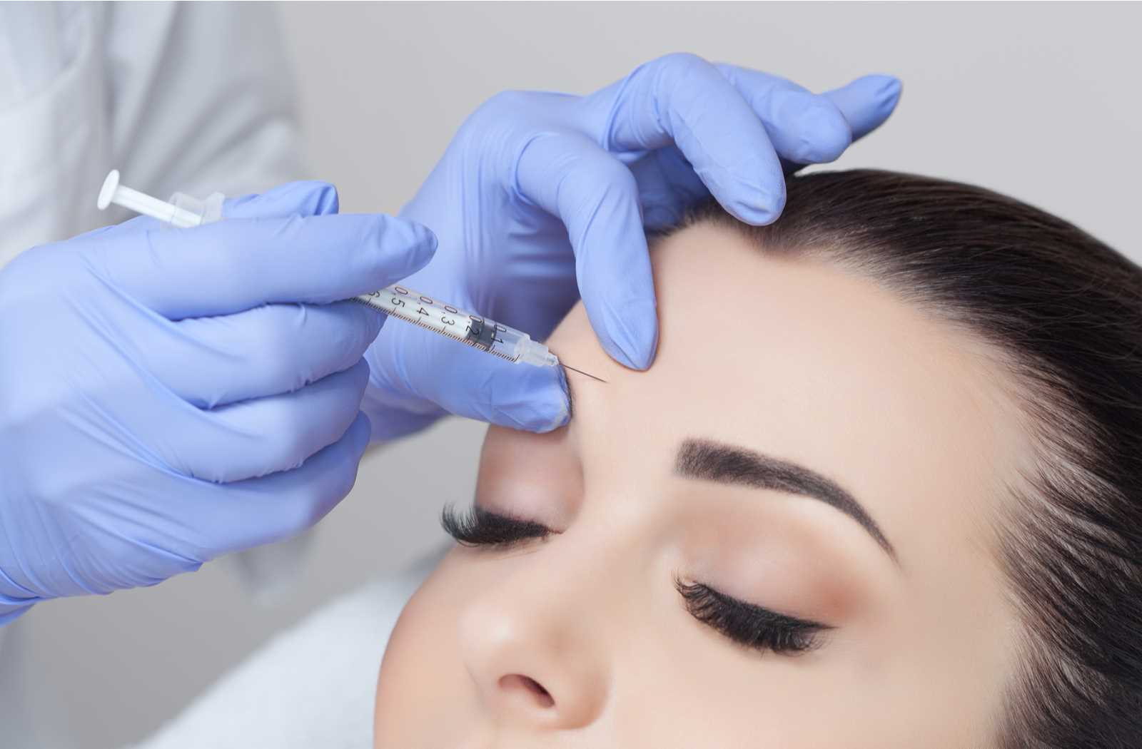 close up of a woman receiving a botox injection to her forehead from hands wearing light blue gloves