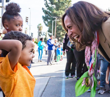 Senator Kamala Harris leans down and smiles broadly at an adorable Black boy of about 5, who smiles excitedly.