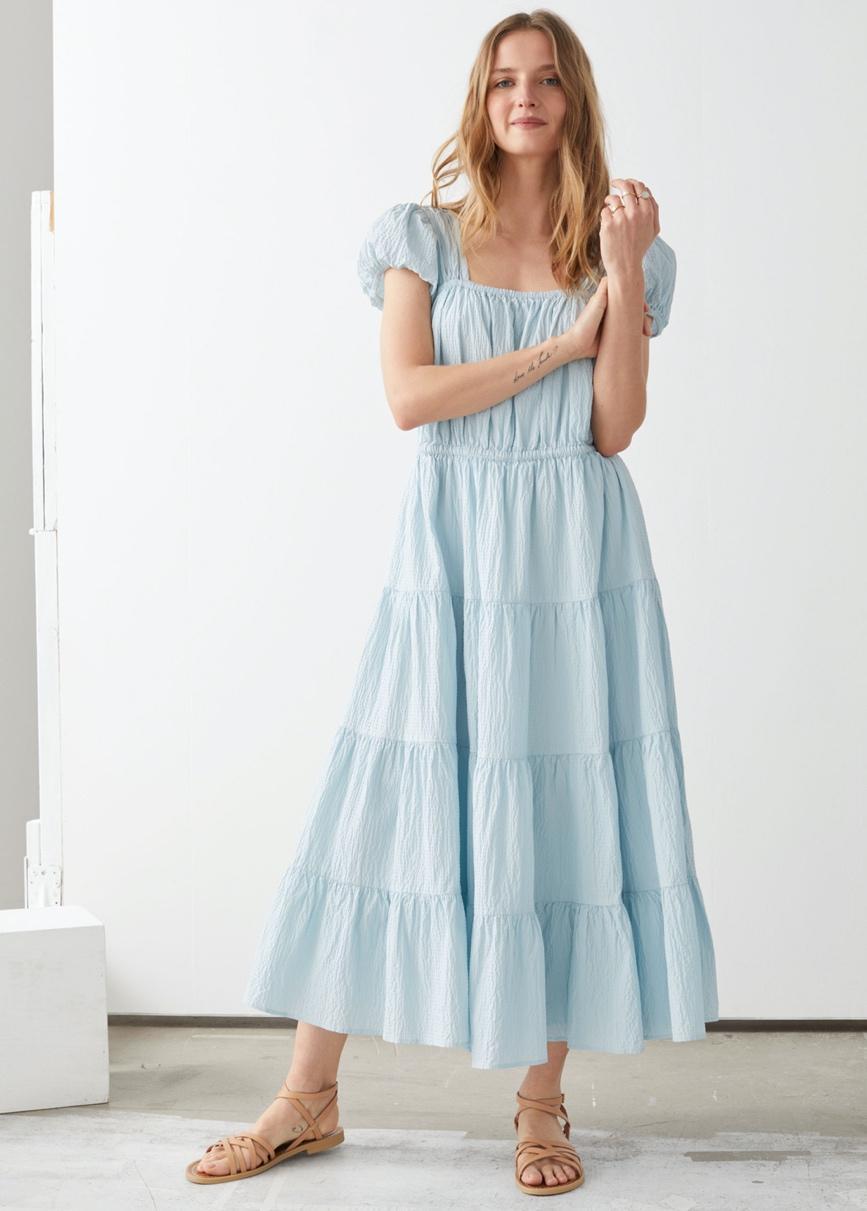 Mujer con vestido blanco  Descripción generada automáticamente