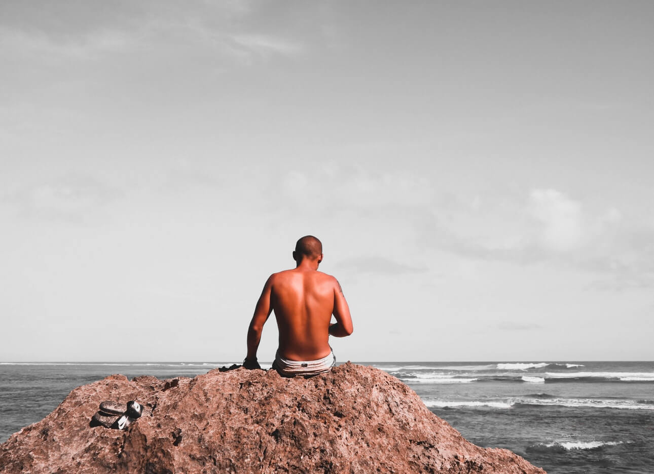 Man sitting on a rock at Greenbowl beach; Bali fitness holiday