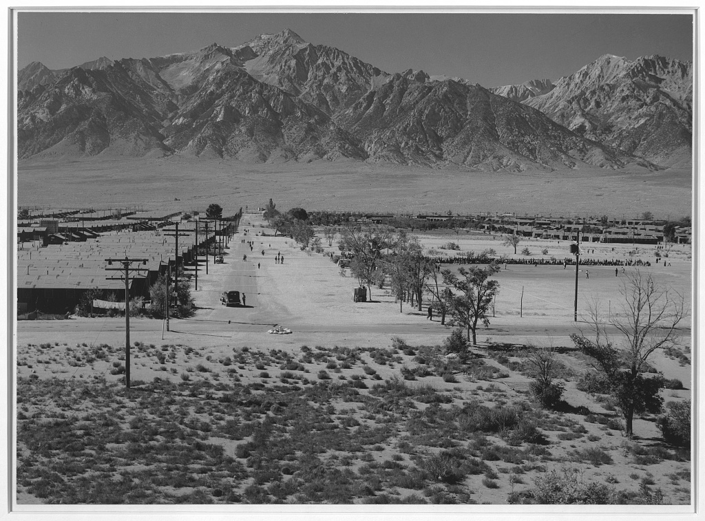 Landscape shot of Manzanar concentration camp, with the Sierra Nevada mountains rising up over the barracks buildings.