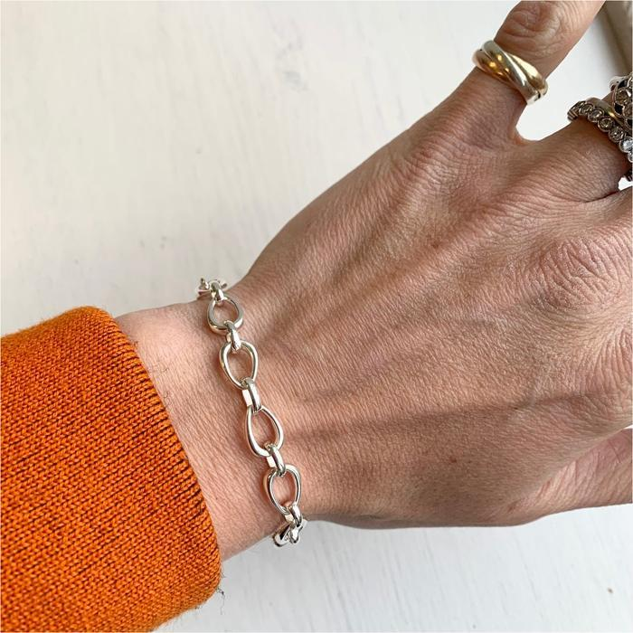 A necklace on a person's wristDescription automatically generated with medium confidence