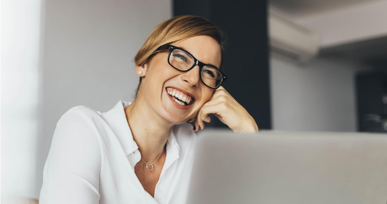 woman smiling and working on a laptop