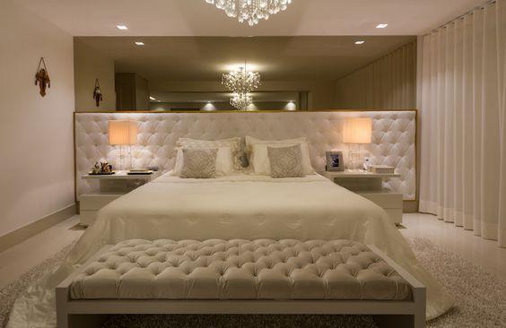 Quarto luxuoso com decoração branca com cabeceira estofada larga pegando toda parede, cama de casal e sofá no pé da cama.