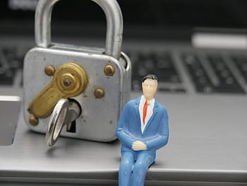 Padlock with male toy in suit sitting on laptop represetning possible cyber crime