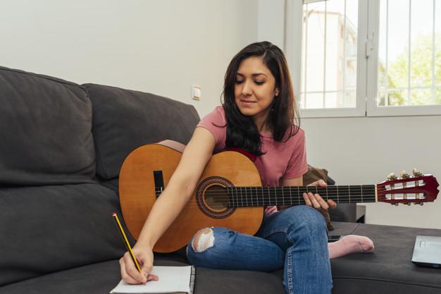 Una mujer sentada en el sofá sosteniendo la guitarra acústica mientras anota las notas musicales