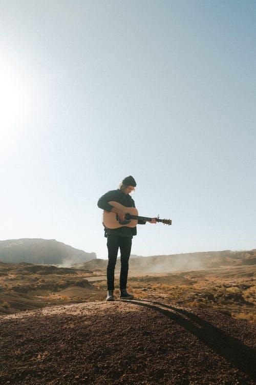 Man playing guitar on rough terrain