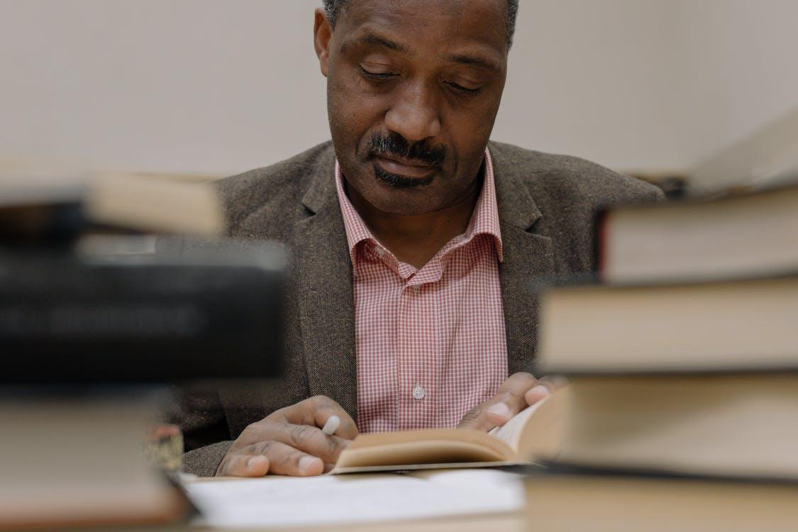 Professor reading a book surrounded by more books