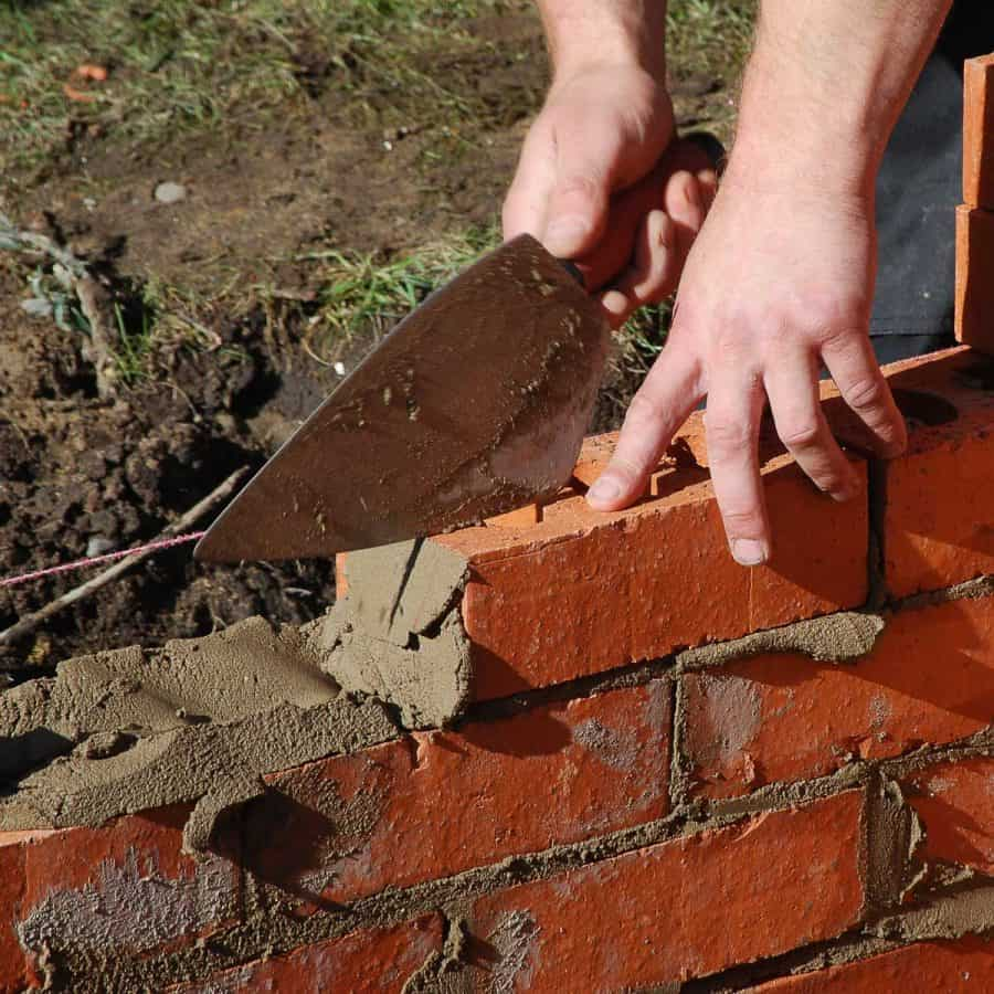 cement vs concrete- person laying bricks with mortar