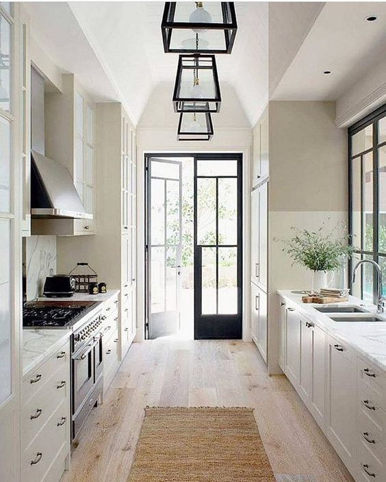 minimalist galley kitchen with white shaker cabinets, white marble countertops, black pendant lights and light wood floors.