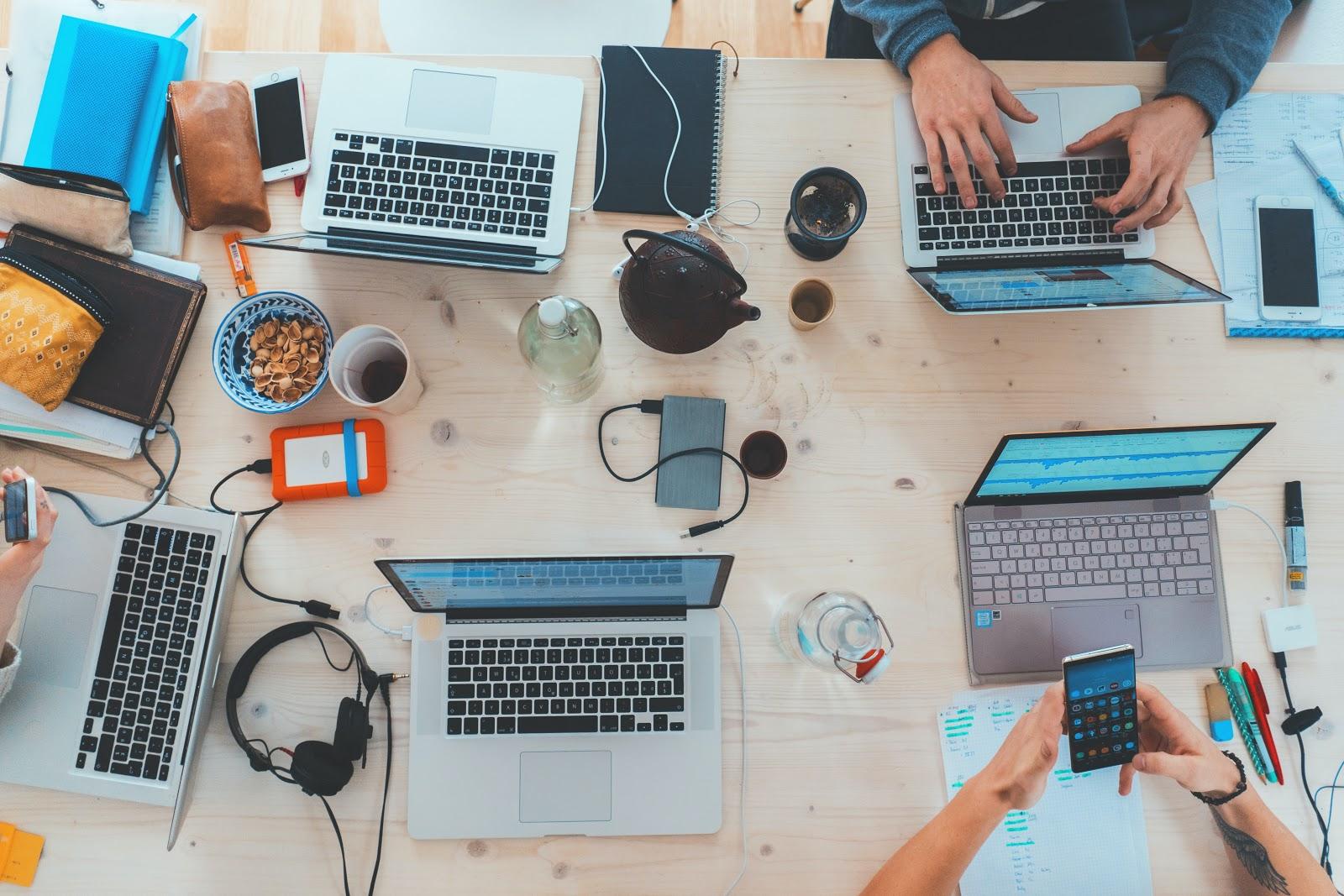 It technicians, laptops on table, taking notes