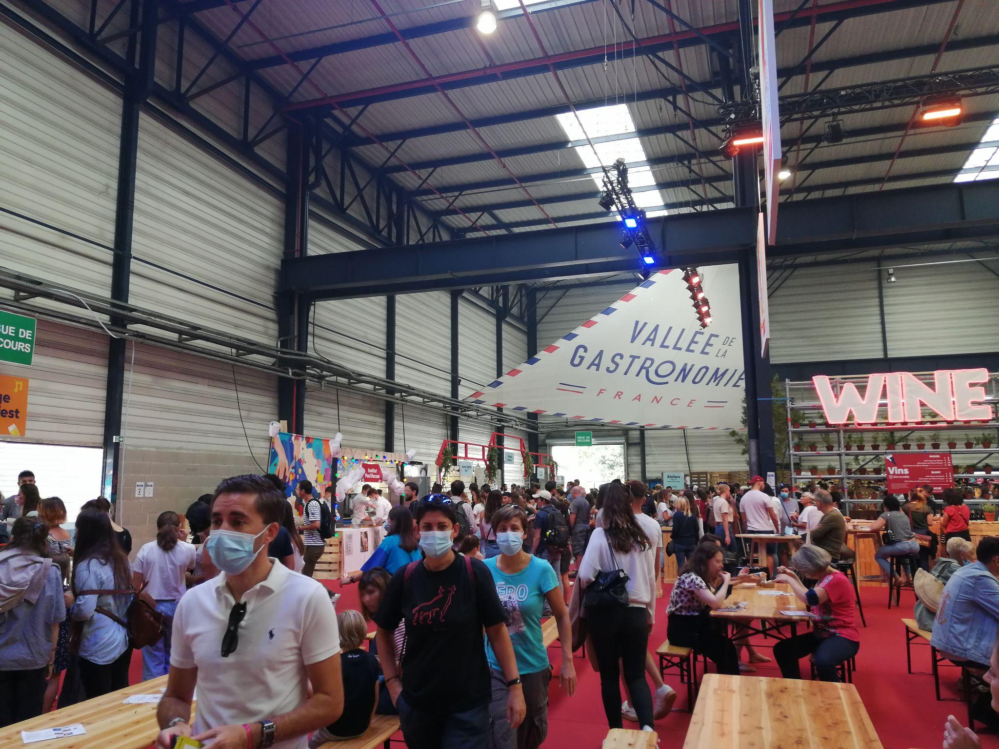 photo prise lors de l'évènement Lyon Street Food Festival 2021. Salle principale avec des participants et des stand de nourriture.