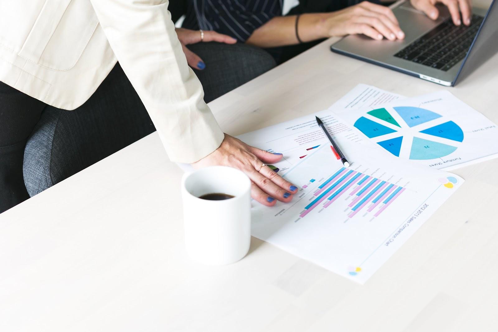 Vários papeis mostrando gráficos com uma mão em cima.