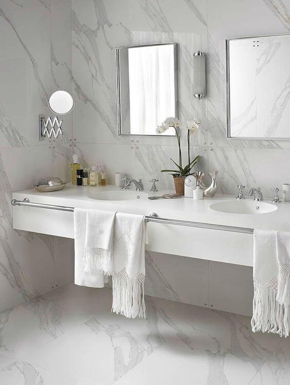 banheiro com revestimento imitando  mármore na parede e piso, bancada da pia branca com detalhes pratas e espelhos com molduras pratas.