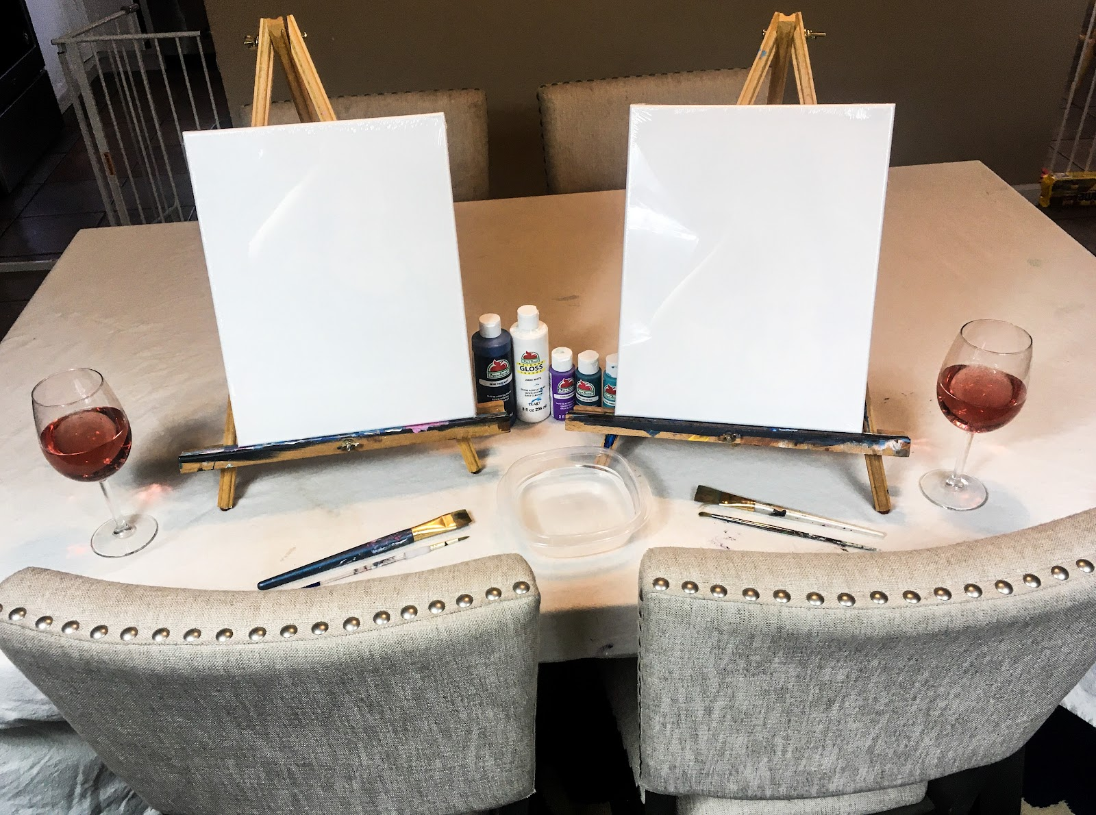 two blank canvases on easels with wine glasses for at home paint and sip night