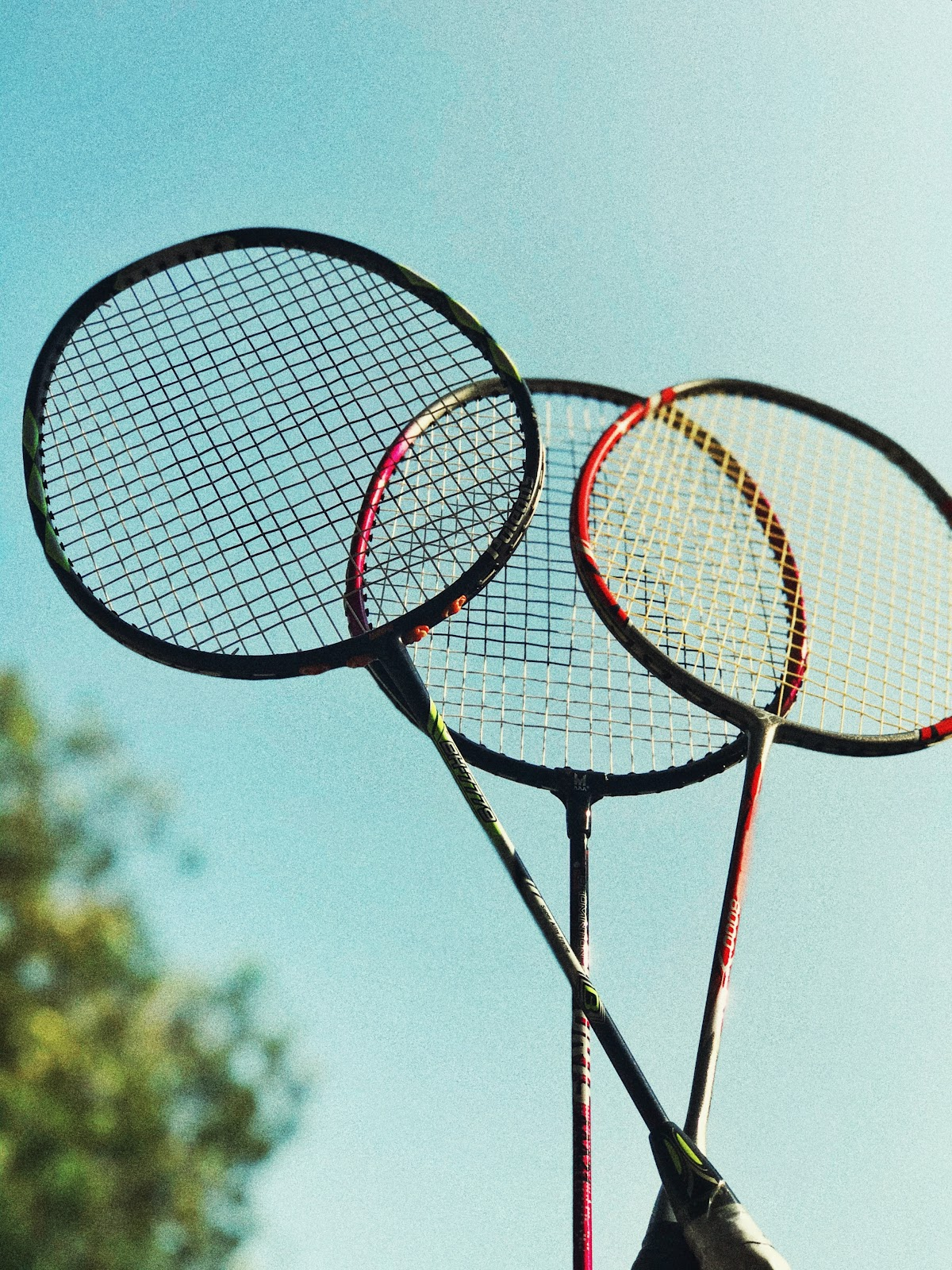 Three badminton rackets raised high against a blue sky.