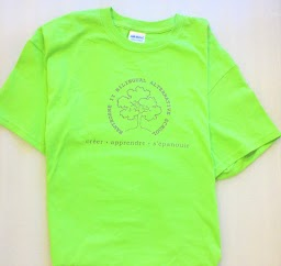 100% cotton Gildan. Youth t-shirts are lime green. Dark grey Hawthorne Logo is centered on front, with three French words across shoulders on back of shirt (créer - apprendre - s'épanouir).