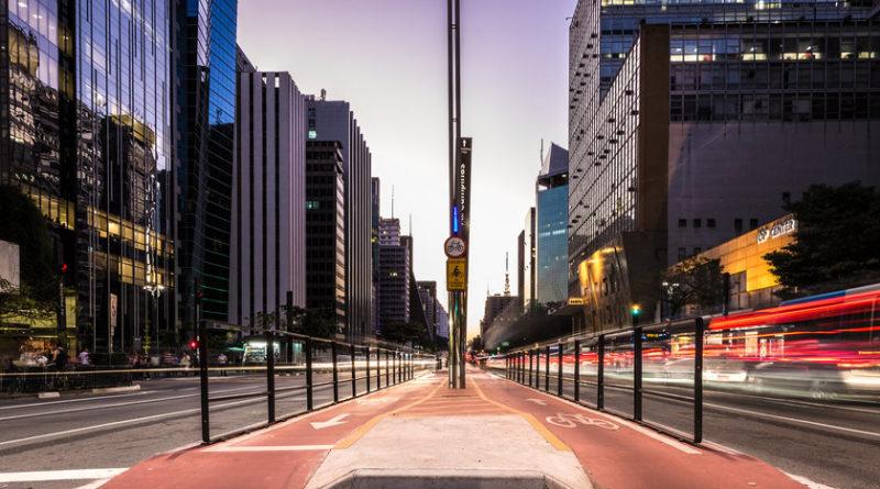 Carros transitando pelas duas vias da Avenida Paulista, um dos principais pontos turísticos de São Paulo. Ao centro, localiza-se a ciclofaixa.