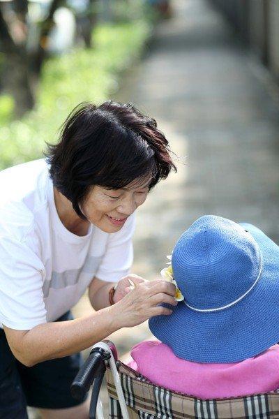 龍應台早上常推著母親坐輪椅去散步,再為她戴上一朵花。 圖/天下雜誌提供