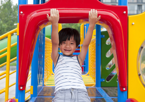 A small boy at the top of a slide on a colorful playground.
