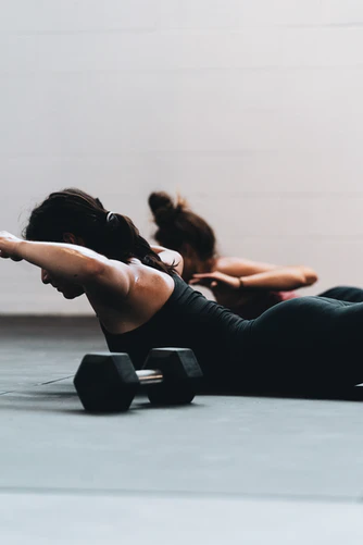 """Two women doing the back extension exercise, also known as the """"Superman"""" and locust pose. This helps relieve sciatica pain by strengthening the back."""