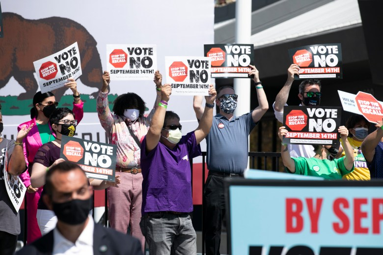 """Gov. Gavin Newsom supporters hold up signs urging voters to vote """"no"""" on the recall during a campaign event at the IBEW-NECA training center in San Leandro on Sept. 8, 2021. Photo by Anne Wernikoff, CalMatters"""