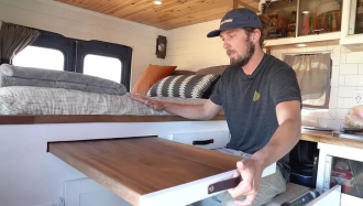 man showing slide out table in ambulance tiny home